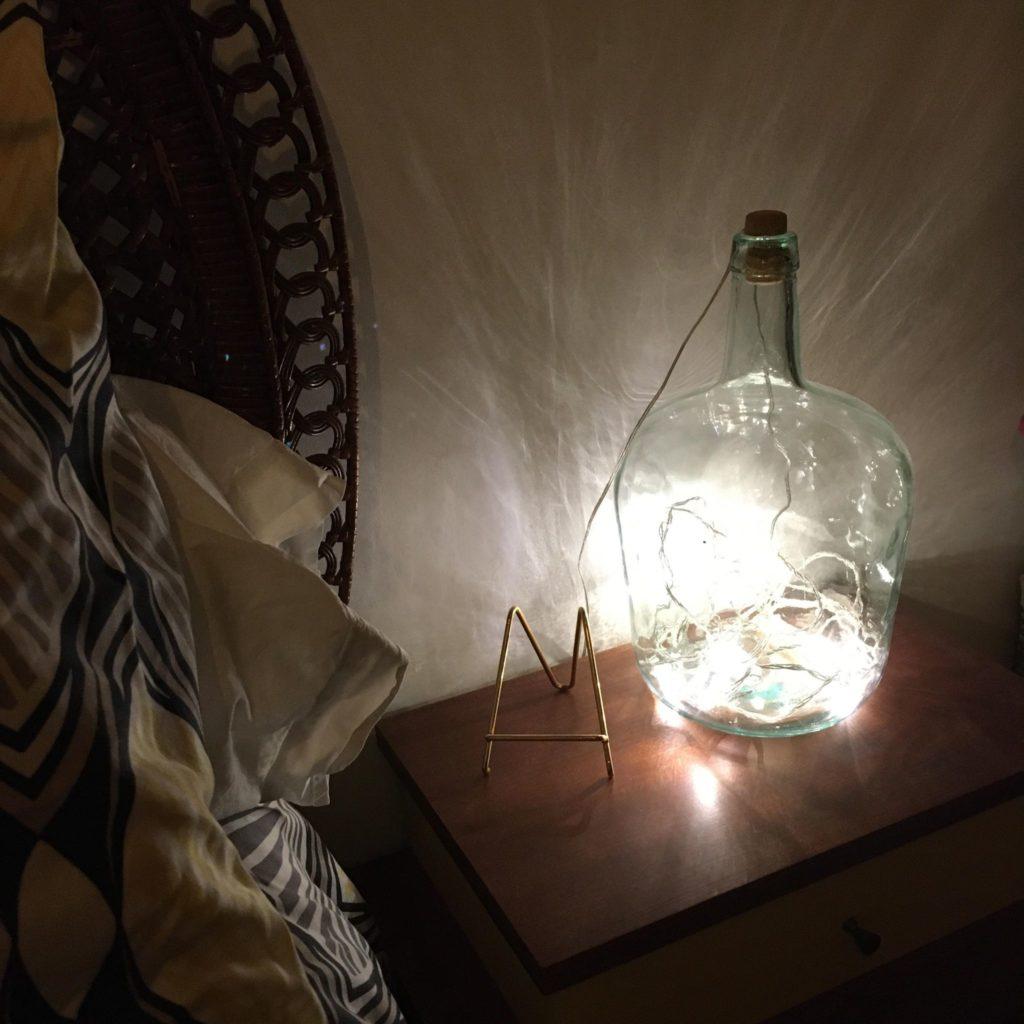 petite bombonne bleutée transformée en lampe de chevet avec une guirlande lumineuse